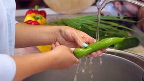 Close-up de pimentas de pimentão da lavagem da moça no dissipador em casa na cozinha vídeos de arquivo