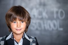 Close-up de pouco menino de escola perto do quadro-negro Foto de Stock Royalty Free