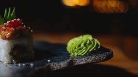 Close-up de rolos de sushi belamente decorados na placa com wasabi Quadro Sushi profissionalmente preparado e decorado imagens de stock royalty free