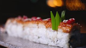 Close-up de rolos de sushi belamente decorados na placa com wasabi Quadro Sushi profissionalmente preparado e decorado imagens de stock