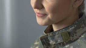 Close up de sorriso da mulher militar nova que sonha da casa, ocupação militar filme