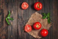 Close-up de tomates frescos, maduros no fundo de madeira Fotografia de Stock Royalty Free