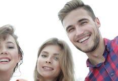 Close up de três jovens que sorriem no fundo branco Imagens de Stock Royalty Free