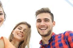 Close up de três jovens que sorriem no fundo branco Fotografia de Stock