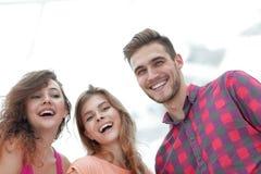 Close up de três jovens que sorriem no fundo branco Foto de Stock Royalty Free