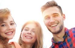 Close up de três jovens que sorriem no fundo branco Fotografia de Stock Royalty Free