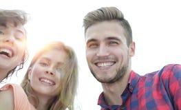 Close up de três jovens que sorriem no fundo branco Foto de Stock