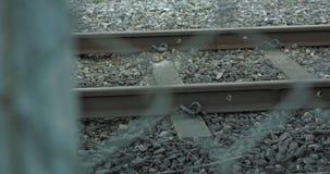 Close up de trilhas do trem com a cerca borrada no primeiro plano video estoque