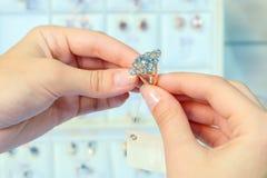Close-up de um anel de diamante do ouro nas mãos de uma moça Seleção da joia na loja Compra e compra O conceito fotos de stock royalty free