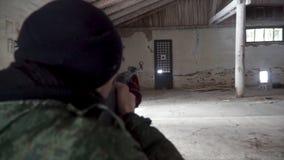 Close-up de um atleta masculino Doing Target Practice grampo equipe apontar de um rifle em um alvo da palha Homem sério considerá Fotografia de Stock