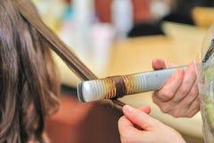 Close-up de um cabeleireiro que endireita o cabelo marrom longo com ferros do cabelo Fotos de Stock Royalty Free