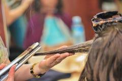 Close-up de um cabeleireiro que endireita o cabelo marrom longo com ferros do cabelo Fotografia de Stock