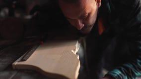 Close-up de um carpinteiro que trabalha em um quadro de janela de madeira com um arquivo em sua oficina video estoque