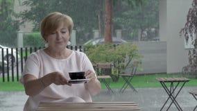 Close-up de um chá envelhecido bonito do gosto da mulher, assento no terraço filme