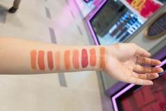 Close up de um comprador fêmea que escolhe a cor selecionada de um batom que tenta em sua pele fotos de stock