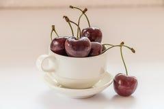Close up de um copo leve enchido com as cerejas doces vermelhas foto de stock
