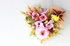 Close-up de um coração de madeira com as rosas da flor e as folhas cor-de-rosa artificiais do verde Fotos de Stock Royalty Free