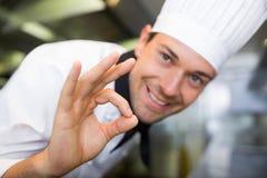 Close up de um cozinheiro masculino de sorriso que gesticula o sinal aprovado Foto de Stock