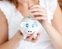 Close-up de um dinheiro da economia da mulher em um piggy-banco Foto de Stock