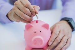 Close-up de um dinheiro da economia do homem de negócios em um mealheiro Fotos de Stock Royalty Free