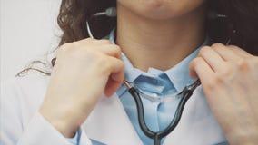 Close-up de um doutor da moça com um phonendoscope Vestido em uma veste branca Uniformemente estando em um fundo cinzento tem vídeos de arquivo