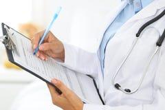 Close-up de um doutor fêmea que enche-se acima do formulário médico na prancheta ao estar em linha reta no hospital Imagens de Stock Royalty Free