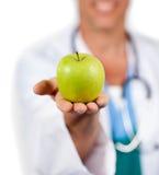 Close-up de um doutor que apresenta uma maçã verde Imagem de Stock Royalty Free