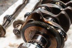 Close-up de um eixo de manivela e de um eixo do carro com as engrenagens e os rolamentos removidos para a substituição em uma ban fotos de stock royalty free