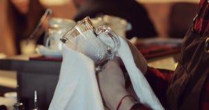 Close-up de um empregado de bar que limpa um copo de vidro com uma toalha branca video estoque