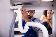 Close-up de um encanador Fixing Sink Pipe fotografia de stock royalty free