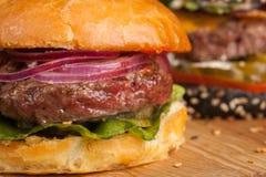 Close up de um grupo do mini hamburguer três caseiro com carne e os vegetais de mármore em uma placa de madeira Imagem de Stock Royalty Free