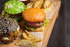 Close up de um grupo do mini hamburguer três caseiro com carne e os vegetais de mármore em uma placa de madeira Fotografia de Stock