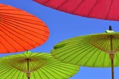 Close-up de um guarda-chuva vermelho, verde e alaranjado do parasol contra o céu azul imagens de stock