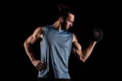 Close up de um halterofilista atlético do homem do poder considerável que faz o exerc fotografia de stock
