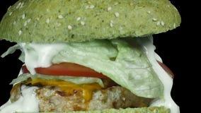 Close-up de um hamburguer suculento grande com um bolo verde polvilhado com o sésamo, girando a câmera de cima para baixo ao long vídeos de arquivo