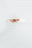 Close up de um homem de negócios que espreita através das cortinas Imagens de Stock Royalty Free