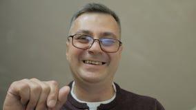 Close-up de um homem de meia idade que se dobre para baixo e negociações maciamente, gesticulando com suas mãos Conceito: um home video estoque