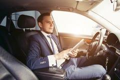 Close up de um homem de negócios novo que usa uma tabuleta em um carro imagens de stock royalty free