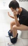 Close-up de um homem no toalete que fala com telefone esperto imagem de stock royalty free