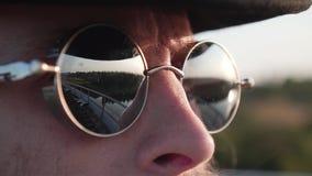 Close-up de um homem nos óculos de sol Tem um bigode Os vidros mostram a paisagem circunvizinha filme