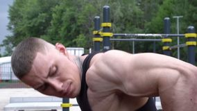 Close-up de um homem novo que faz impulso-UPS nas barras exteriores filme