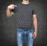 Close-up de um homem que aponta seu dedo em um t-shirt cinzento vazio Imagem de Stock Royalty Free