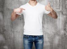 Close-up de um homem que aponta seu dedo a um t-shirt vazio, e o polegar acima Imagens de Stock Royalty Free