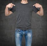 Close-up de um homem que aponta seus dedos em um t-shirt cinzento vazio foto de stock royalty free