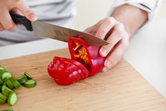 Close-up de um homem que corta a pimenta vermelha na cozinha fotos de stock royalty free