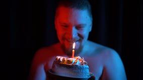 Close-up de um homem que funde para fora uma vela em um bolo em um fundo preto video estoque