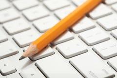 Close up de um lápis em um teclado Fotografia de Stock