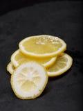 Close up de um limão cortado com açúcar Fresco, ácido, suculento, saudável, o amarelo cortou ingredientes do limão no fundo preto Fotografia de Stock Royalty Free