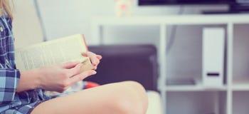 Close-up de um livro nas mãos de uma menina que senta-se no sofá no fundo interior home imagens de stock