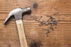 Close up de um martelo e uma pilha dos rebites, pregos no fundo branco imagens de stock
